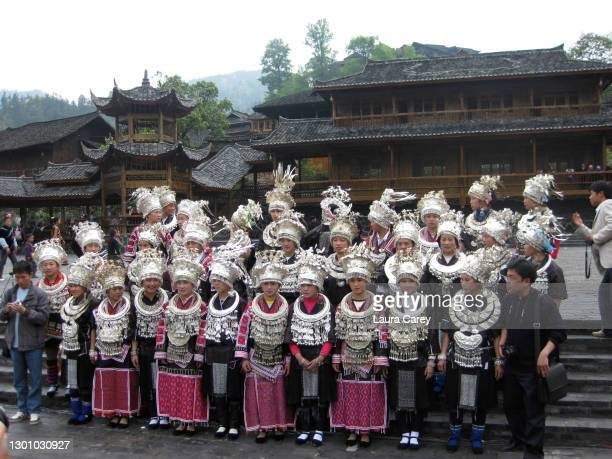 Local people from the Miao Minority in traditional dress and handmade silver headdresses gather in the town square in preparation for music and...