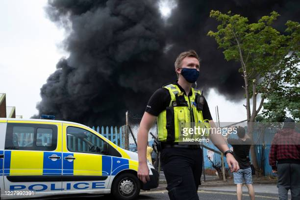 Local people gather to witness a massive scale fire at a plastics factory at Tyseley Industrial Estate on 10th August 2020 in Birmingham United...