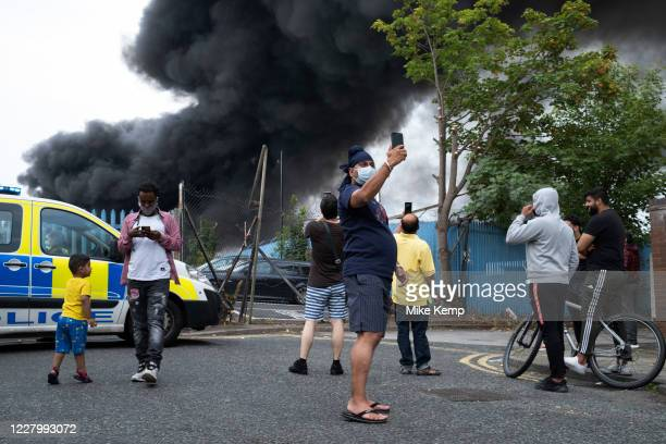Local people gather to witness a massive scale fire at a plastics factory at Tyseley Industrial Estate on 10th August 2020 in Birmingham, United...