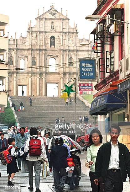 Local people head home at the end of the day 18 December against the backdrop of the facade of the Church of Sao Paulo one of the main tourist sites...