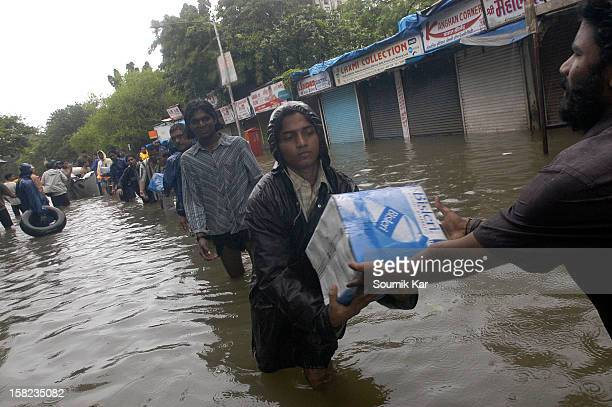 Local people help in distributing bottled water to those affected by floods in Air India Colony, Santacruz East, Mumbai, 2005.