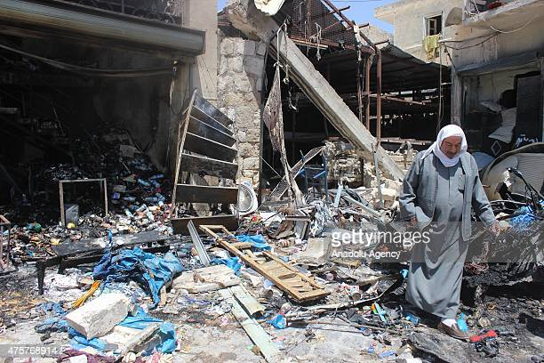 Local people inspect rubble of houses and shops after a helicopter belonging to the Syrian army carried out barrel bomb attacks on the residential...