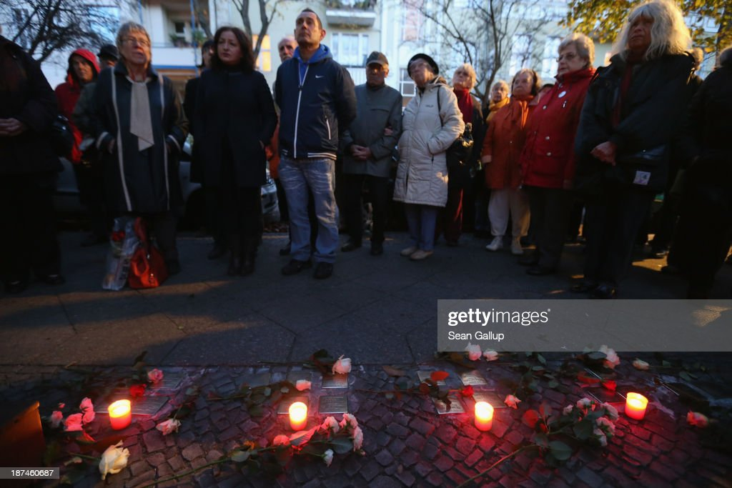 Local people on a commemorative walk in Friedenau district listen to stories about Jews who once lived in this street while standing by candles placed at Stolpersteine on the 75th anniversary of the Kristallnacht pogroms on November 9, 2013 in Berlin, Germany. Stolpersteine are concrete cobblestones afixed with brass plaques that memorialize local Jewish residents who were murdered or expelled by the Nazis during the Holocaust. Events are taking place across Germany today and tomorrow to commemorate the day in 1938 when Nazi gangs across Germany and Austria burned down over 1,000 synagogues, smashed Jewish-owned businesses, looted Jewish residences and killed several hundred Jews. Anti-Semitism was a central component of Adolf Hitler's rise to power and won him wide-spread sympathy among ordinary Germans and Austrians.