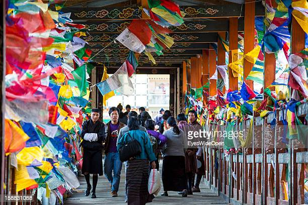 Local people passing a bridge to a marketplace, decorated with hundreds of prayer flags on November 18, 2012 in Thimphu, Bhutan.