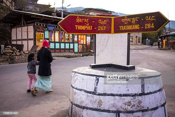 Local people passing the main junction with a sign to Thimphu on November 18 2012 in Bumthang Bhutan