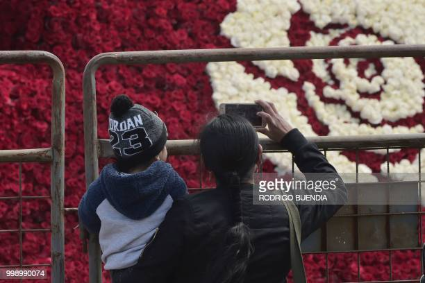 Local people visit the floral pyramid where more than 500000 roses were set in order to run for a Guinness World Record in Tabacundo Ecuador on July...
