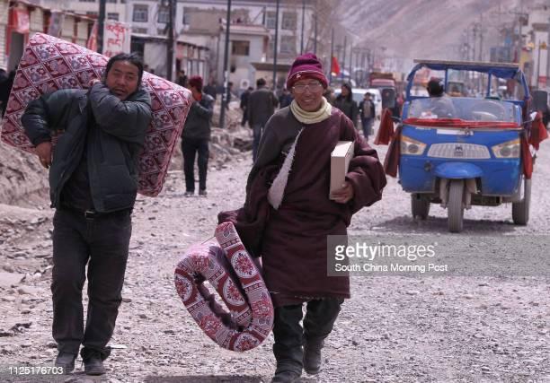 Local people walk one the main street near Gesaer Square in Jiegu, Yushu, Qinghai, April 10, 2011. A devastating 7.1-magnitude earthquake hit Yushu,...