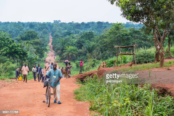 local people walking on a rural unpaved road, dr congo - congo stock pictures, royalty-free photos & images