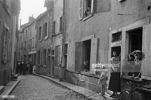 Local people watch as a group of British pilgrims passes through a French town on its way to the Benedictine abbey at Vezelay August 1946 The...