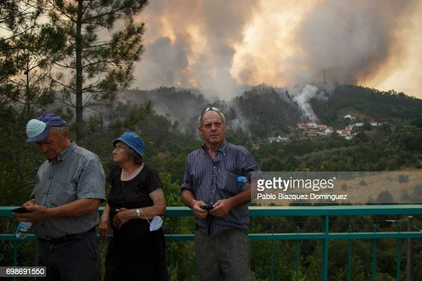 Local people watch how flames approach to Mega Fundeira village after a wildfire took dozens of lives on June 20 2017 near Picha in Leiria district...