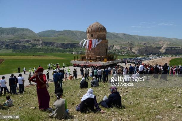 Local people watch the tomb of Zenyel Bey while it is carried on a rolling structure on May 12 at Hasankeyf in Batman southeastern Turkey as it is...