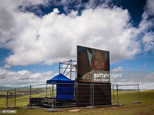 Local people watches the Mandela funeral service on a large television situated on a hilltop overlooking the service in the valley below Qunu South...