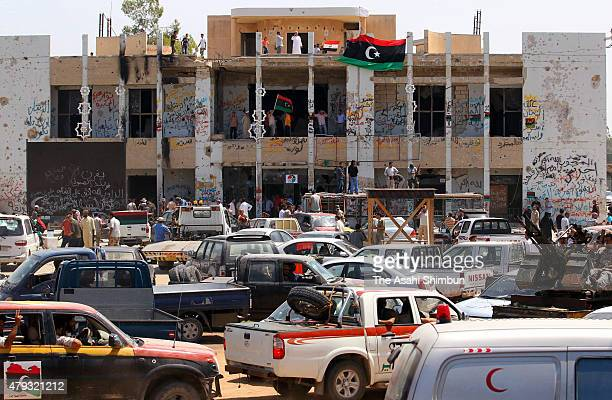 Local people wave flags of the National Transition Council at the residence of Muammar Gaddafi after the battle of Tripoli during the Libyan Civil...