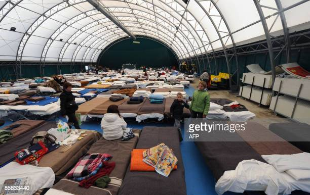 Local people who were evacuated following a violent earthquake the day before wake up after spending the night in a shelter set up in a gymnasium of...