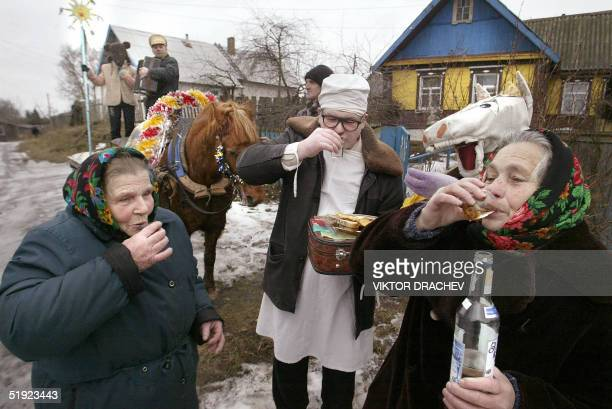 Local people with a horse carriage drink vodka while carolsinging on a street of the town of Lepel some 180 km from the capital Minsk 07 January 2005...