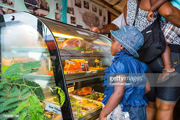 Local people with their babies pupils and farmers buying and selling goods meat sweets or livestock on a marketplace on October 21 2012 in...
