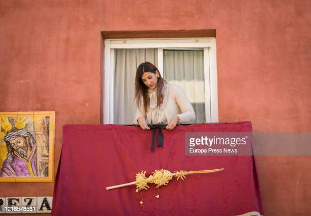Local person of Sevilla is seen decorating her balcony with hangings and palms despite the suspension of Easter celebrations on April 03, 2020 in...