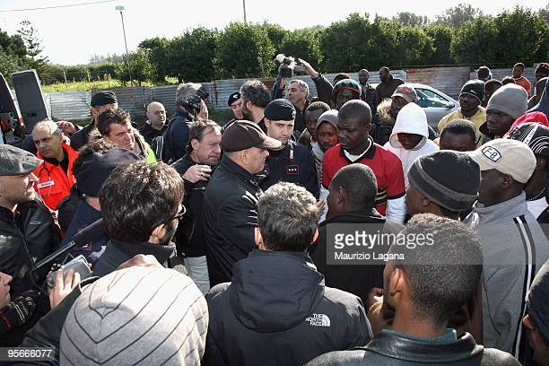 A local police chief speaks with migrants as they arrive to be evacuated by bus to Crotone after two days of riots during which 37 people were...