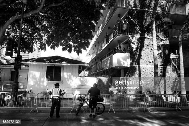 Local police officers stand guard against an empty viewing pen outside US President Donald Trump's hotel in Honolulu Hawaii on November 3 as a few...