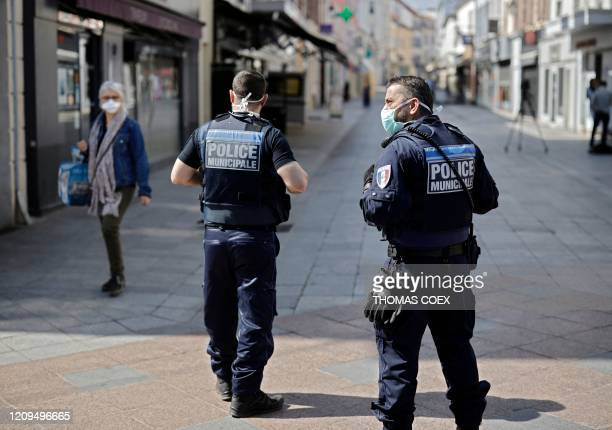 Local police patrol as pedestrians wear face masks in the main street of Sceaux, south of Paris, on April 8 on the 23rd day of a strict lockdown in...