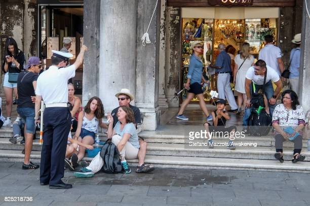 A local police tells a family of tourist with their lunch to move away from Saint Mark's Square on August 1 2017 in Venice Italy Over 30 million...