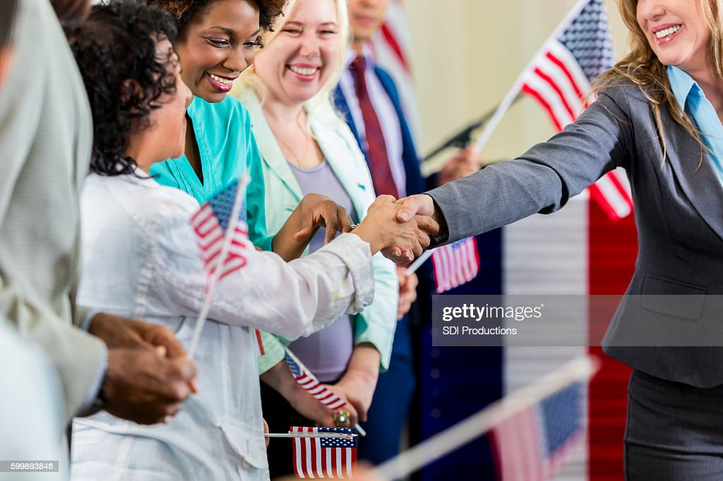Local political candidate shaking hands with supporters at event : Stock Photo