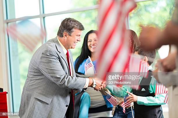 Local politician shaking hands and greeting supporters at event