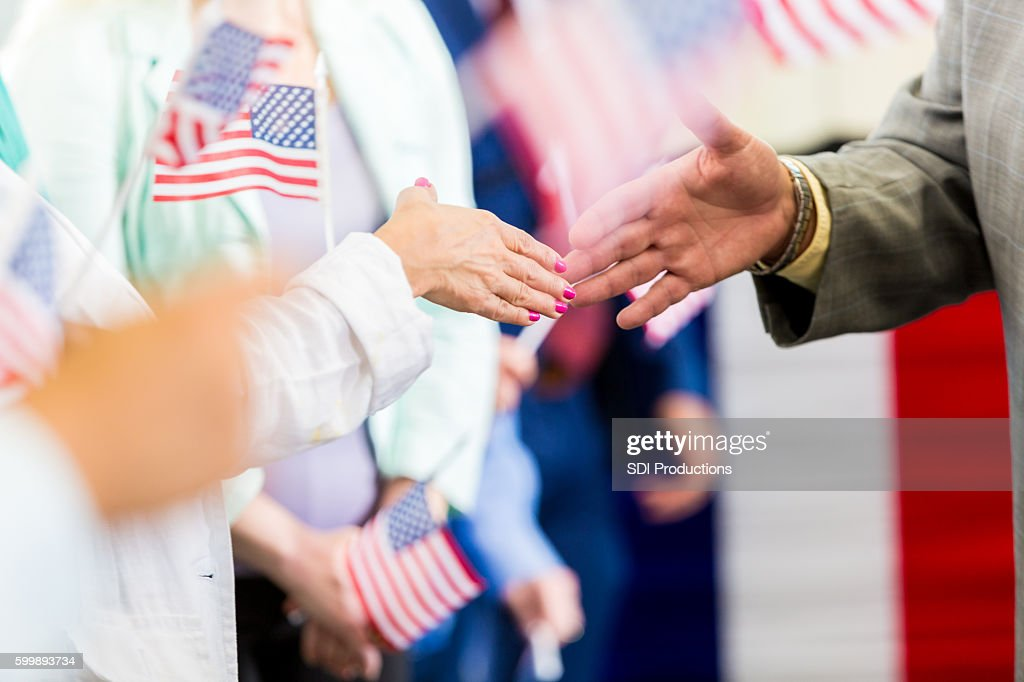 Local politician shaking hands with supporters at event : Stock Photo