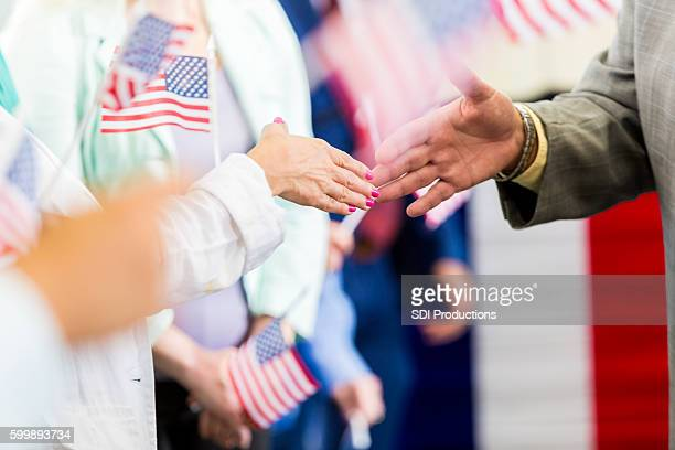 Local politician shaking hands with supporters at event