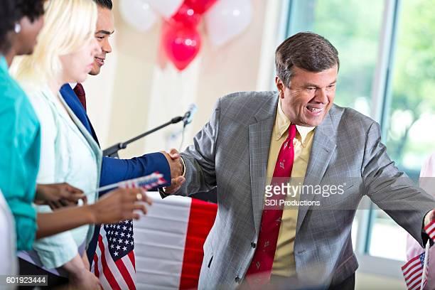 local politician shaking hands with supporters at event - riunione municipale foto e immagini stock