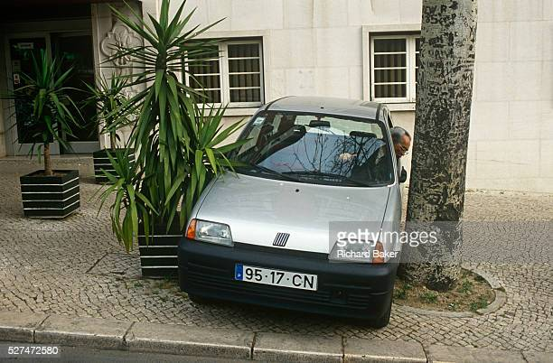 A local Portuguese man reverses his Fiat car into a narrow space between two trees on a Lisbon street pavement Squeezing between the shrub and the...