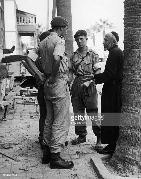 A local priest talks to British soldiers in Port Said during the Suez Crisis November 1956