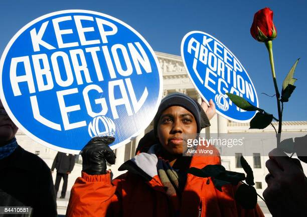 Local prochoice activist Lisa King holds a sign in front of the US Supreme Court as a prolife activist holds a rose nearby during the annual March...