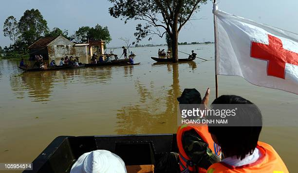 A local Red Cross team moving on a boat loaded with instant noodles and clean water aproaches a group of villagers waiting for relief aid at a...
