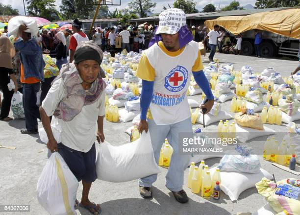 Local Red Cross volunteer helps an evacuee carry sack of rice during a food distribution by the International Committee of the Red Cross on January...
