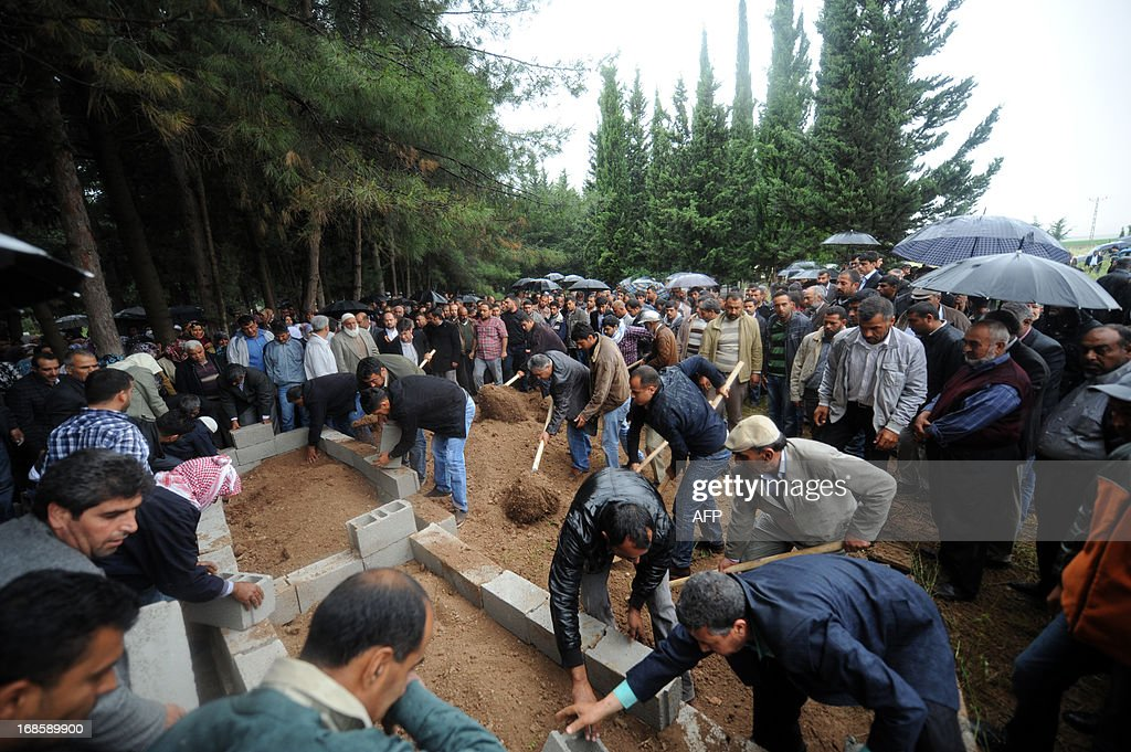 Local relatives mourn on May 12, 2013 at the graves of victims of a car bomb which went off on May 11 at Reyhanli in Hatay just a few kilometres from the main border crossing into Syria. Turkey was reeling from twin car bomb attacks which left at least 43 people dead in a town near the Syrian border, with Ankara blaming pro-Damascus groups and vowing to bring the perpetrators to justice. A Syrian minister denied on May 12 accusations that Damascus was behind a bomb attack in a Turkish town that left dozens dead, a day after Ankara blamed supporters of President Bashar al-Assad for the blasts.