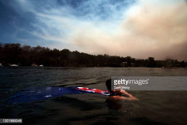 Local resident Brodey Coulter cools off in the fire affected Clyde River near Batemans Bay on January 26, 2020 in Nellingen, Australia. Australia...
