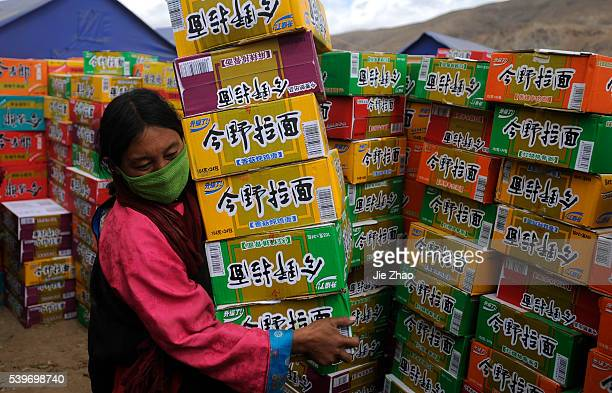 Local resident carries instant noodles near the tents in the earthquake-hit Gyegu town of Yushu County, Qinghai province April 20, 2010. VCP