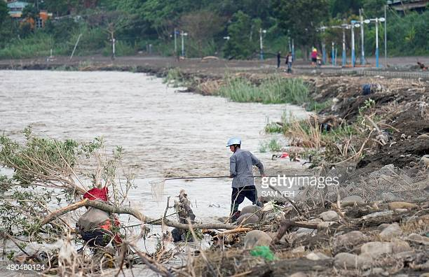 Local resident catches fish with a net from the Xindian river after Typhoon Dujuan passed in the New Taipei City on September 29, 2015. Super typhoon...
