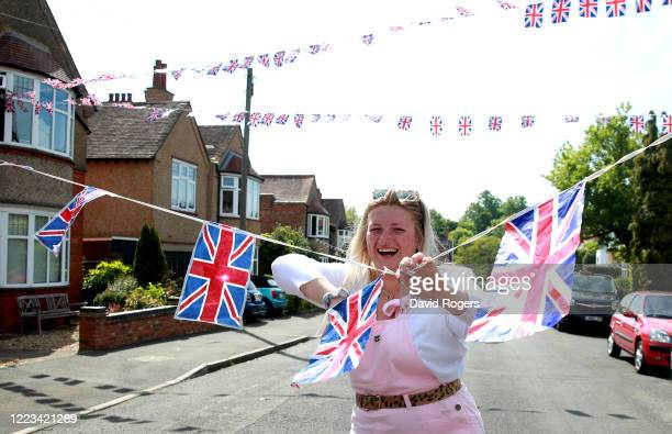 Local resident Clarrie Jackson prepares the flag bunting on May 07 2020 in Northampton United Kingdom The UK will commemorate the 75th Anniversary of...