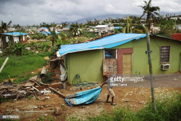 A local resident cleans debris near his damaged home in an area without electricity on October 15 2017 in San Isidro Puerto Rico Puerto Rico is...