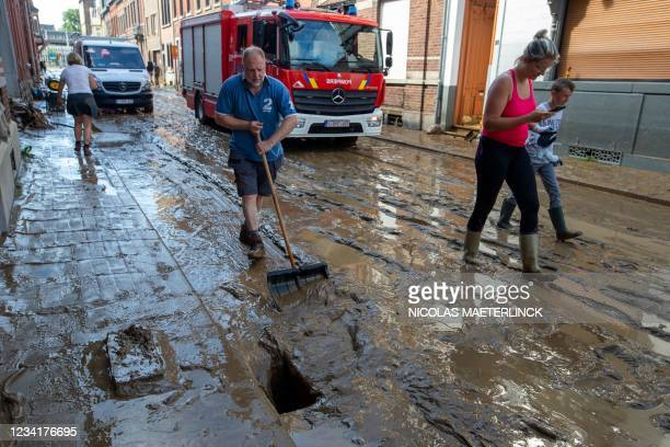 Local resident cleans the mud covering the street in Namur, on July 25 after the heavy rainfall of July 24. - In mid-July western Europe was hit by...
