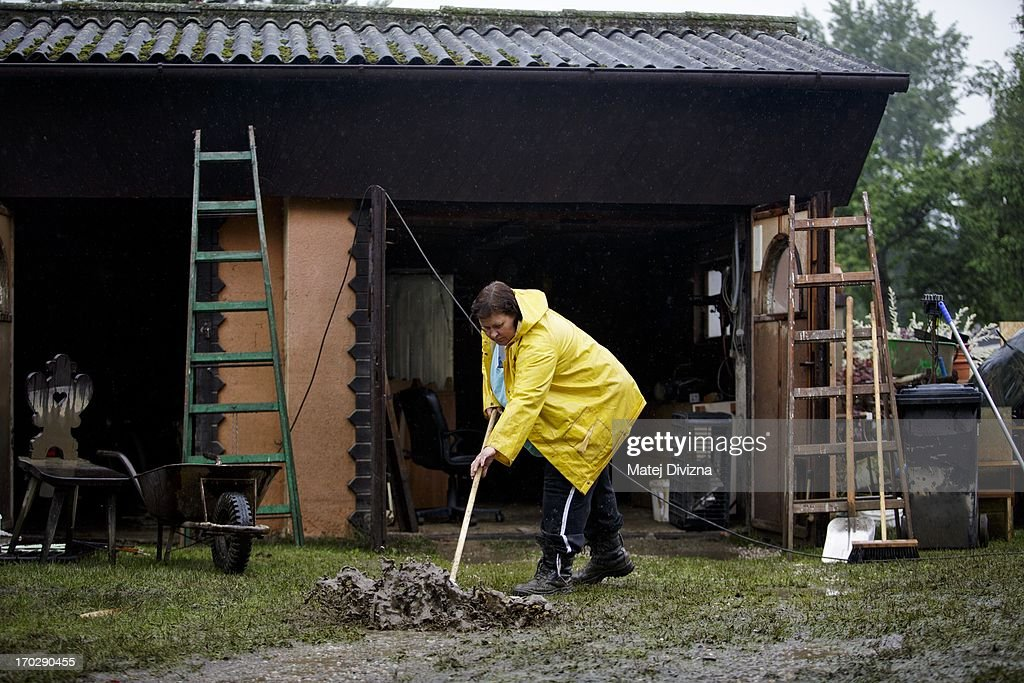 A local resident cleans up in front of her house during a rainy day after flooding from Vltava River on June 10, 2013 in Luzec, Czech Republic. As river levels in Czech Republic decrease expectations of flooding increase in Northern Germany triggering more evacuations.