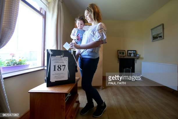 TOPSHOT Local resident Colleen Ui Fhioruisce with her twoyearold daughter Saoirse at the ballot box as she votes on Gola Island off the Donegal coast...