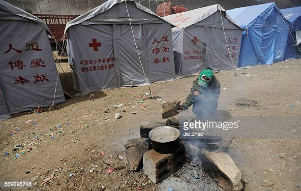 Local resident cooks near the tents in the earthquake-hit Gyegu town of Yushu County, Qinghai province April 20, 2010. VCP