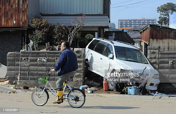 A local resident cycles past a car damaged by the tsunami in Tagajo Miyagi prefecture on March 13 2011 two days after a massive 89 magnitude...