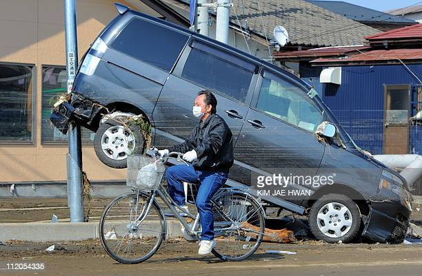 A local resident cycles past a car damaged in the tsunami on a street in Tagajo Miyagi prefecture on March 13 2011 two days after a massive 89...