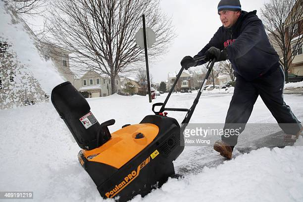 Local resident Dean Sosa cleans up snow in front of his house February 13 2014 in Alexandria Virginia Up to 12 inches of snow fell over the...