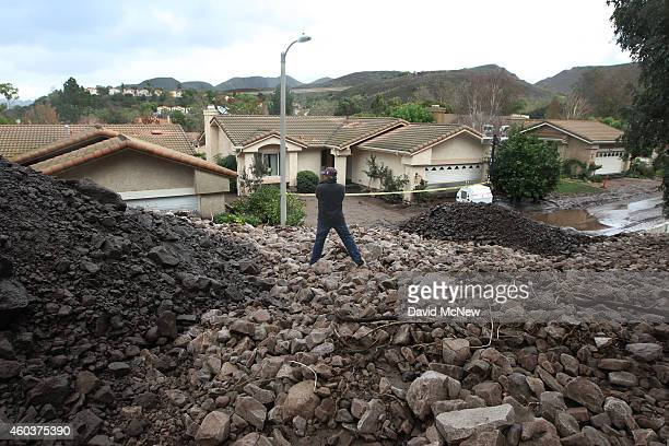 Local resident Erwin Fodran surveys damage from atop a pile of rocks and mud after debris flows smashed into houses as a powerful storm that has been...