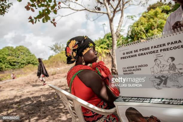 A local resident holds her child as a mozambican nurse explains contraception methods and sexual education during an health point gathering organised...